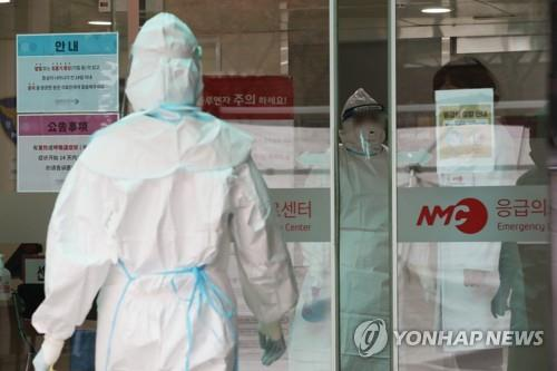 Medical workers at the National Medical Center wear protective masks and suits as they prepare to check people for the novel coronavirus on Jan. 29, 2020. (Yonhap)