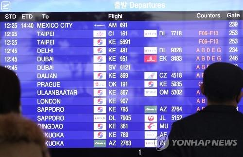 This undated file photo shows travelers looking at flight details at Incheon International Airport, west of Seoul. (Yonhap)