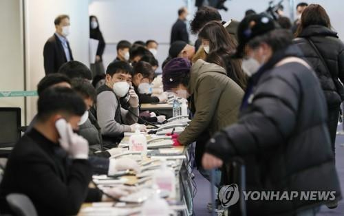 Passengers arriving from China register their domestic contact details with South Korean officials at Incheon International Airport, west of Seoul, on Feb. 5, 2020. (Yonhap)