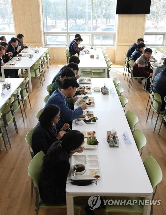 Employees of Suwon Urban Development Corp. eat lunch seated only on one side of the table at the corporation's building in Suwon, just south of Seoul, on March 2, 2020, amid concern over the spread of the new coronavirus. (Yonhap)