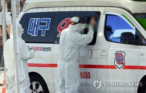 A medical staffer takes a sample from a potential COVID-19 patient aboard an ambulance at a makeshift drive-thru clinic for coronavirus patients in Daegu, 300 kilometers south of Seoul, on March 6, 2020. (Yonhap)