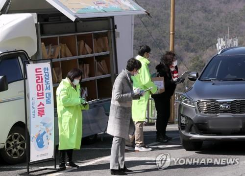 Officials of the Busan Metropolitan Library lend books to citizens in a drive-thru on March 11, 2020. (Yonhap)