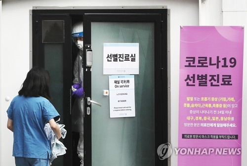 This file photo shows an official of the National Medical Center conveying medical supplies to a COVID-19 screening clinic in Seoul on March 3, 2020. (Yonhap)
