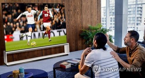 In this photo provided by LG Electronics Inc. on March 8, 2020, models watch a football match on the company's 8K OLED TV. (PHOTO NOT FOR SALE) (Yonhap)