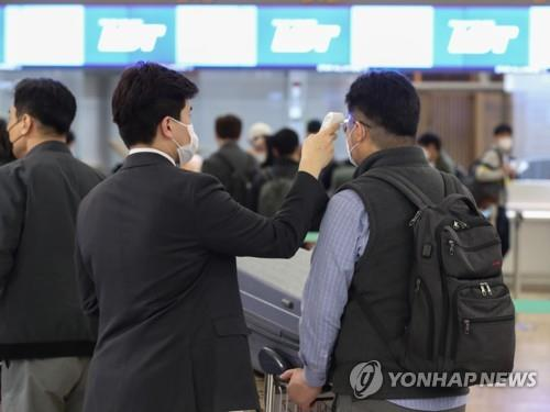 An LG Chem worker (R) undergoes a body temperature check before boarding a special flight to Poland at Incheon International Airport, west of Seoul, on April 17, 2020. (Yonhap)