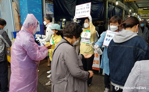 This photo provided by the city of Tongyeong shows local officials and volunteers holding a hand sanitation campaign at a market in the southwestern coastal city on May 3, 2020. (PHOTO NOT FOR SALE) (Yonhap)