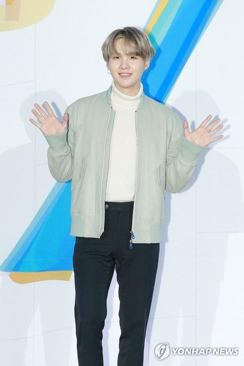 In this file photo provided by Big Hit Entertainment, BTS member Suga waves at reporters during a press conference at the Convention and Exhibition Center (COEX) in southern Seoul on Feb. 24, 2020. (PHOTO NOT FOR SALE) (Yonhap)
