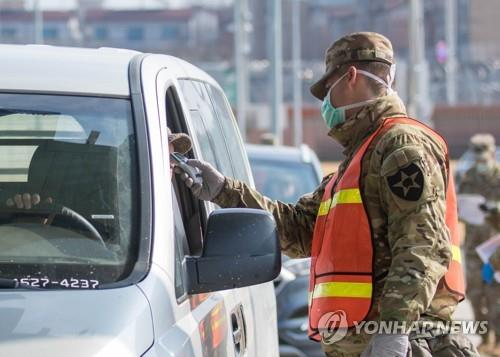 A military guard at U.S. Army Garrison Humphreys in Pyeongtaek, 70 kilometers south of Seoul, checks the temperature of a driver to screen entrants to the compound for the novel coronavirus on Feb. 28, 2020, in this photo provided by U.S. Forces Korea. (PHOTO NOT FOR SALE) (Yonhap)