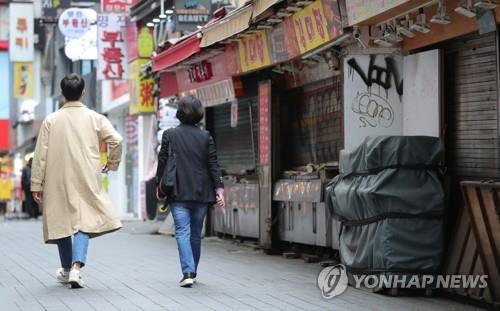 People walk past shuttered shops in Myeongdong, a popular shopping district in central Seoul, on May 19, 2020. (Yonhap)