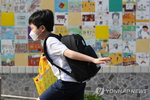 A young student runs toward a school in Seoul's Yongsan Ward on June 8, 2020, as schools reopen in full swing. (Yonhap)