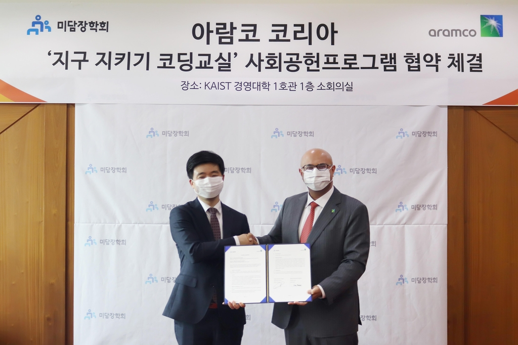 This photo, provided by Aramco Asia Korea, shows its Representative Director Fahad A. Al-Sahali (R) shaking hands with Jang Neung-in, MIDAM's standing director, after signing a partnership agreement for coding programs at the KAIST College of Business in Seoul. (PHOTO NOT FOR SALE) (Yonhap)