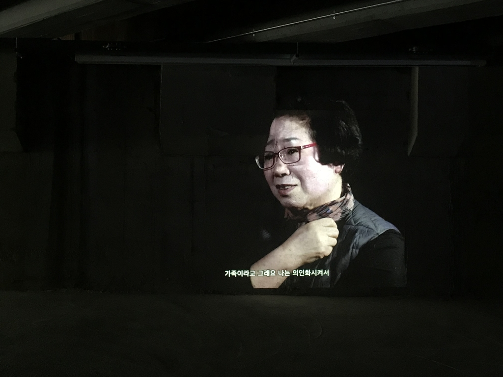 "This July 28, 2020, screenshot shows an old tenant of Yujin Sangga, a 50-year-old residential and commercial building in eastern Seoul, speaking about the building in an interview shown at the ""Hongje Yuyeon"" exhibition in the building's basement. (Yonhap)"