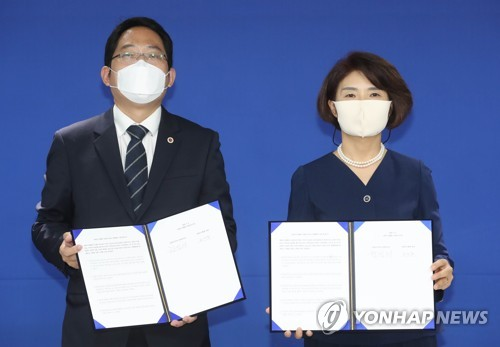 Korean Medical Association head Choi Dae-zip (L) and ruling Democratic Party policy committee chief Rep. Han Jeoung-ae hold up signed agreements outlining future talks to resolve the government's medical reform plan and end the strike by doctors, in Seoul on Sept. 4, 2020. (Yonhap)