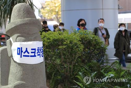 This file photo shows a stone mascot of Jeju Island wearing a mask as tourists pass by. (Yonhap)