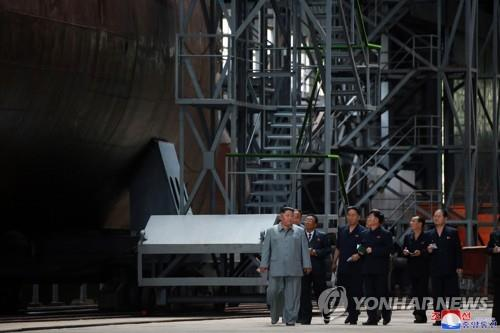 This photo, released by the Korean Central News Agency on July 23, 2019, shows North Korean leader Kim Jong-un (L) inspecting a newly built submarine. As is customary, the agency didn't provide the date and location. (For Use Only in the Republic of Korea. No Redistribution) (Yonhap)
