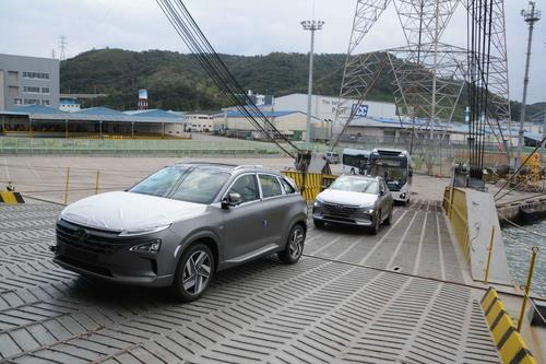 This photo taken on Sept. 28, 2020, and provided by Hyundai Motor shows two Nexo hydrogen fuel cell electric vehicles and two hydrogen Elec City buses being loaded onto a ship for export to Saudi Aramco at the carmaker's port in Ulsan, 414 kilometers southeast of Seoul. (PHOTO NOT FOR SALE) (Yonhap)