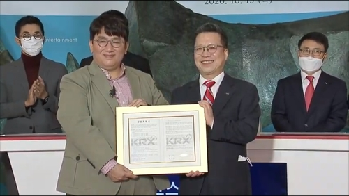 This photo, captured from Big Hit Entertainment's live video channel, shows Chairman and CEO Bang Si-hyuk (L) and Korea Exchange (KRX) Chairman and CEO Jung Ji-won posing for photos at the K-pop entertainment giant's listing ceremony held at KRX's Seoul headquarters on Oct. 15, 2020. (Yonhap)
