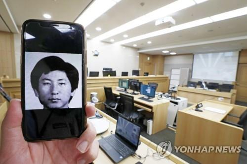 This photo shows a courtroom at Suwon District Court in Suwon, south of Seoul, where on Nov. 2, 2020, Lee Chun-jae (shown in the image on the mobile phone), the suspect in one of the nation's most notorious serial killings, testified about his rape and murder of a 13-year-old girl in 1988 during the retrial of a man who was convicted and served 20 years in prison in the case. (Yonhap)