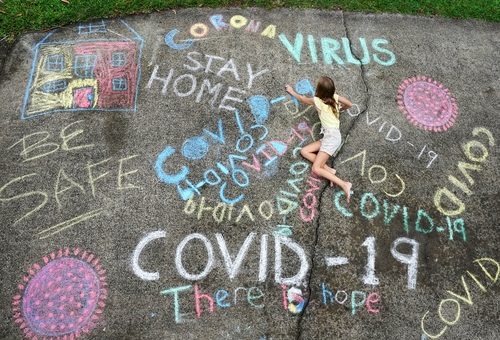This photo, provided by Dave Hunt of the Australian Associated Press, shows a girl drawing and writing letters with chalk at a house in the Gold Coast. (PHOTO NOT FOR SALE)(Yonhap)