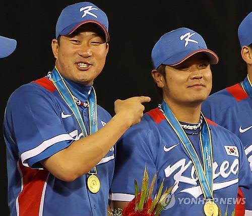 In this file photo from Nov. 19, 2010, Bong Jung-keun (L), captain of the South Korean baseball team, teases his teammate Choo Shin-soo for crying during the medal ceremony of the Guangzhou Asian Games, following South Korea's 9-3 victory over Chinese Taipei in the gold medal game at Aoti Baseball Field in Guangzhou, China. (Yonhap)