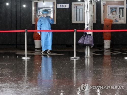 Medical workers wait for visitors to receive coronavirus tests at a makeshift clinic in front of Seoul Station on May 4, 2021. (Yonhap)