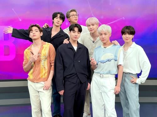 This photo, posted on BTS' official Twitter account, shows the group posing at a studio during its appearance on SBS News on July 24, 2021. (PHOTO NOT FOR SALE) (Yonhap)