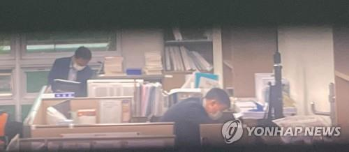 This photo provided by the office of Rep. Kim Woong of the main opposition People Power Party shows investigators from the Corruption Investigation Office for High-ranking Officials combing through the lawmaker's office at the National Assembly in Seoul on Sept. 10, 2021, as part of a probe into a political meddling scandal allegedly involving one of the PPP's presidential contenders and ex-Prosecutor General Yoon Seok-youl. (PHOTO NOT FOR SALE) (Yonhap)