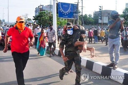 7日、インド南部のLGポリマース工場近くでガス中毒で倒れた住民を移送する救助。 [AFP =連合ニュース]
