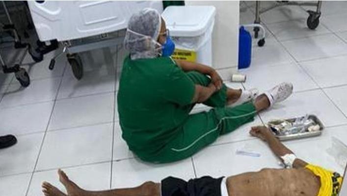 코로나 사망자 옆에 앉아 울고 있는 브라질 간호사
