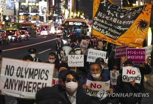 (도쿄 EPA=연합뉴스) 신종 코로나바이러스 감염증(코로나19) 상황에서 추진되는 2020도쿄올림픽 개최에 반대하는 일본 시민들이 25일 도쿄 도심에서 '노 올림픽' '올림픽보다 생명이 중요' 등의 문구가 적힌 손팻말을 들고 시위하고 있다.