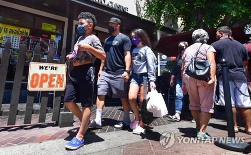 14일(현지시간) 미 LA 시내의 식당 앞을 사람들이 마스크를 쓴 채 지나가고 있다. [AFP=연합뉴스]