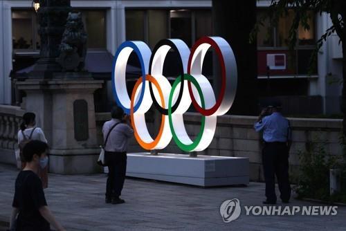 (도쿄=연합뉴스) 이지은 기자 = 도쿄올림픽 개막 8일을 앞둔 15일 오후 일본 도쿄 도심에 설치된 오륜마크 조형물을 한 시민이 사진 찍고 있다. jieunlee@yna.co.kr