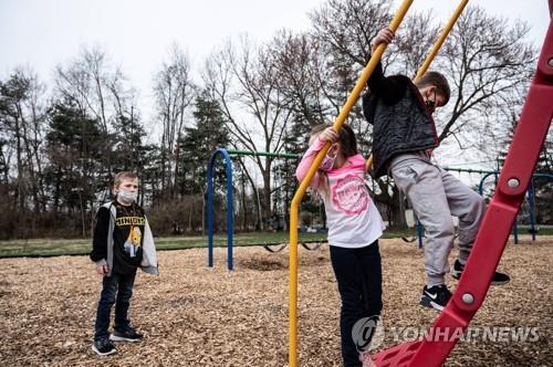 미국 켄터키주 한 초등학교의 놀이터에서 마스크를 착용한 채 놀이하는 학생들 [AFP=연합뉴스]