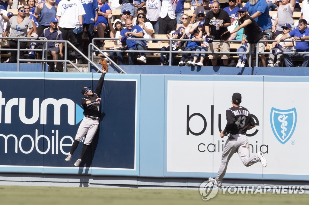 In this Associated Press photo, Colorado Rockies center fielder Garrett Hampson (L) tries to catch a home run by Ryu Hyun-jin of the Los Angeles Dodgers in the bottom of the fifth inning of a Major League Baseball regular season game at Dodger Stadium in Los Angeles on Sept. 22, 2019. (Yonhap)