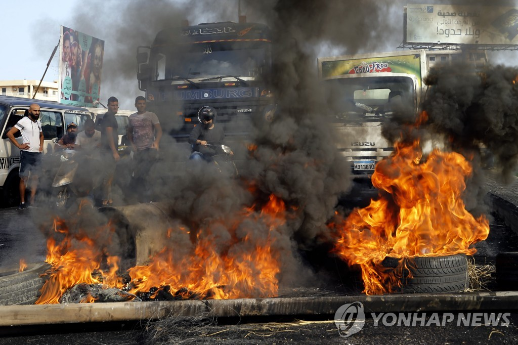 This Associated Press photo shows people standing by their cars as they try to cross a highway blocked by anti-government protesters by burning tires, during protests against the government, in Khaldeh, south of Beirut, Lebanon, on Nov. 14, 2019. (Yonhap)