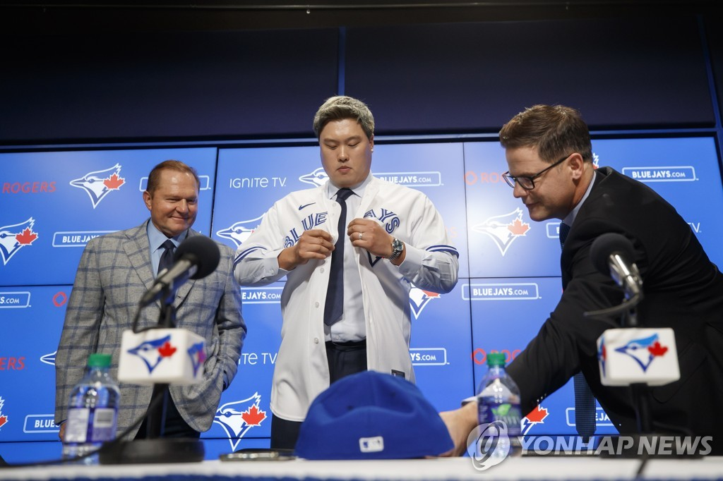In this Canadian Press photo via the Associated Press from Dec. 27, 2019, Ryu Hyun-jin (C) puts on his new jersey for the Toronto Blue Jays during his introductory press conference at Rogers Centre in Toronto. Ryu is flanked by his agent Scott Boras (L) and Blue Jays' general manager Ross Atkins. (Yonhap)