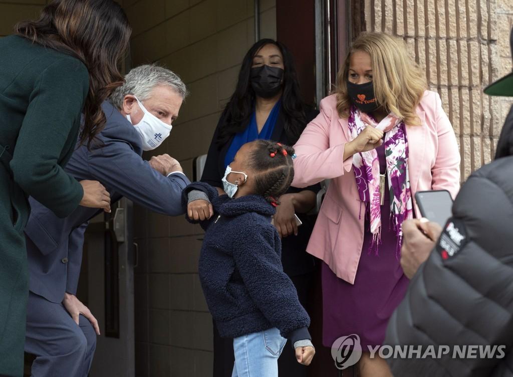 뉴욕 브루클린의 한 학교에서 마스크를 쓴 채 학생과 팔꿈치 인사하는 빌 더블라지오 뉴욕시장