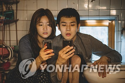 "This film still shot, provided by CJ Entertainment, shows the protagonists of Director Bong Joon-ho's ""Parasite"" trying to search for a free Wi-Fi network at their basement home. (PHOTO NOT FOR SALE) (Yonhap)"