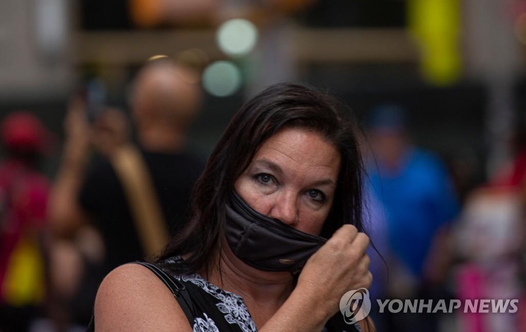 29일(현지시간) 미국 뉴욕의 한 여성이 마스크를 착용하고 있다. [AFP=연합뉴스]