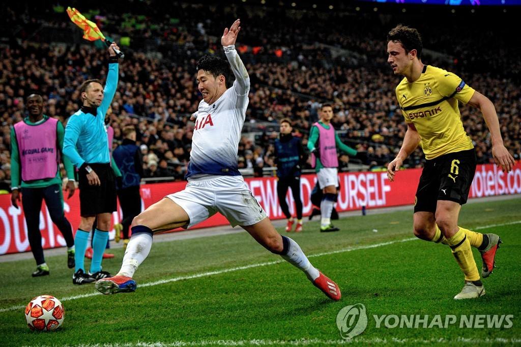 In this EPA photo, Son Heung-min of Tottenham Hotspur (L) chases a loose ball past Thomas Delaney of Borussia Dortmund during their UEFA Champions League round of 16 match at Wembley Stadium in London on Feb. 13, 2019. (Yonhap)