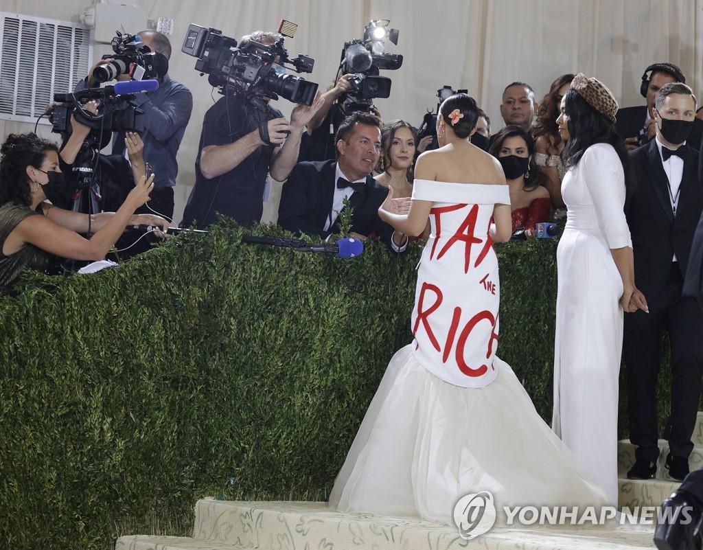 알렉산드리아 오카시오-코르테즈(민주당) 의원이 멧 갈라서 '부자들에게 과세하라'(Tax the rich)적힌 흰색 드레스를 입고 기자들의 질문에 답하고 있다. [EPA=연합뉴스]