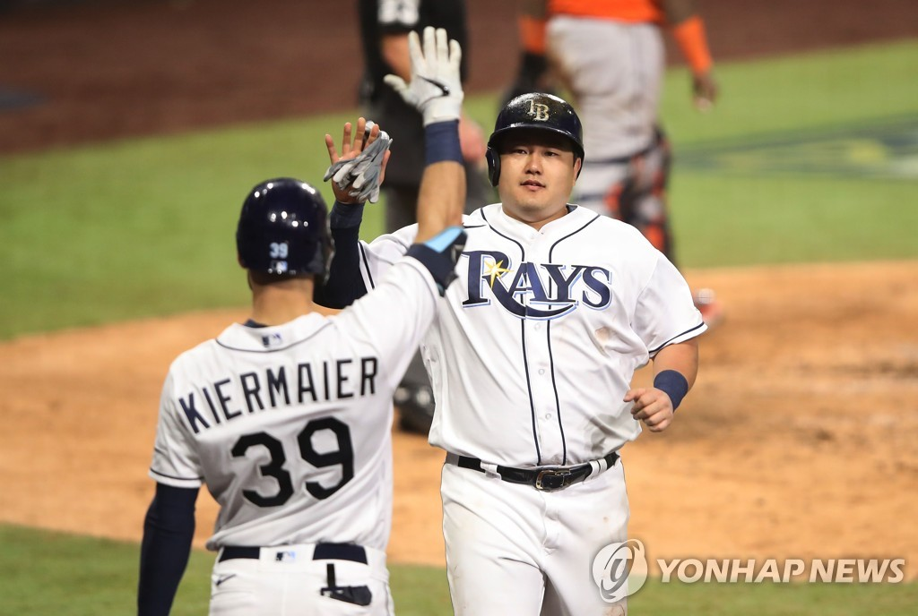 In this Getty Images photo, Choi Ji-man of the Tampa Bay Rays (R) celebrates with teammate Kevin Kiermaier after scoring on a Mike Zunino sacrifice fly against the Houston Astros during the bottom of the sixth inning of Game 7 of the American League Championship Series at Petco Park in San Diego on Oct. 17, 2020. (Yonhap)