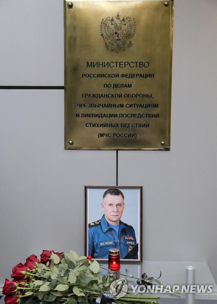 러시아 비상사태부 밖에 걸린 지니체프 장관의 사진과 꽃 [타스=연합뉴스]