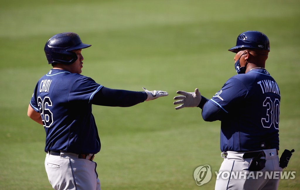 In this USA TODAY Sports photo via Reuters, Choi Ji-man of the Tampa Bay Rays (L) reaches for the hand of his first base coach Ozzie Timmons after drawing a walk against the Houston Astros during the bottom of the second inning of Game 5 of the American League Championship Series at Petco Park in San Diego on Oct. 15, 2020. (Yonhap)