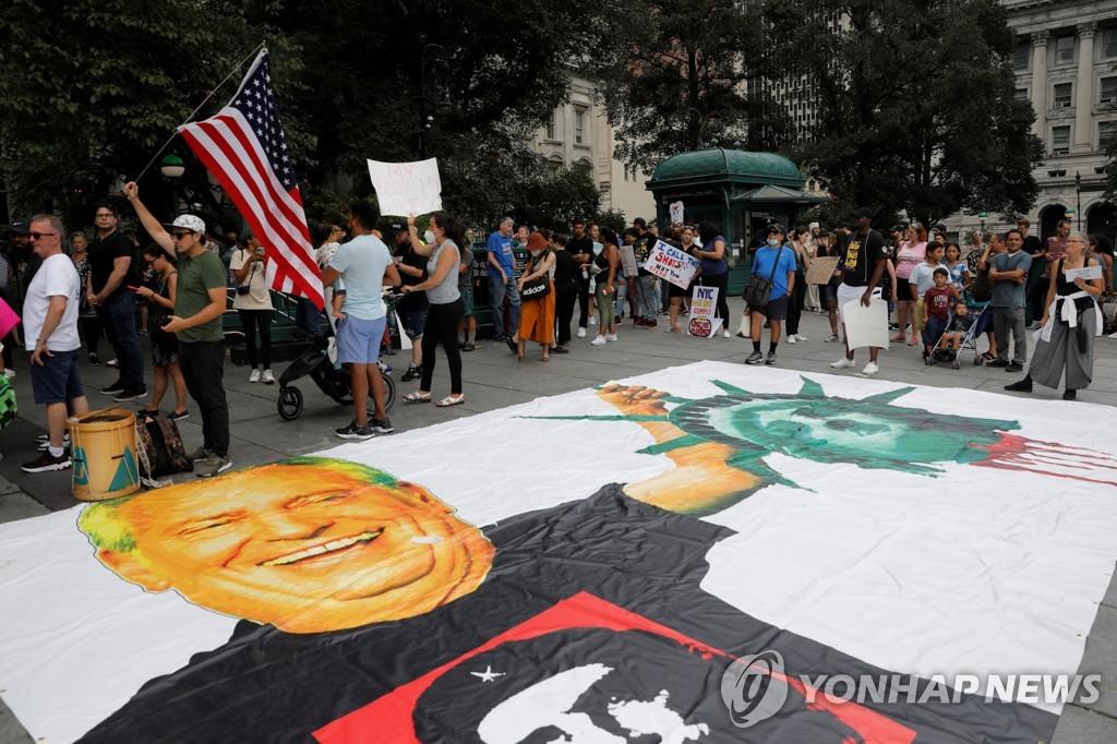 뉴욕시청 앞에 빌 더블라지오 시장의 합성사진을 놓고 백신 의무화를 반대하는 시위대