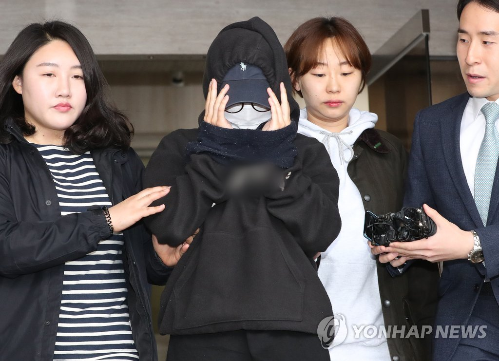 The suspect in nude photo leak case (second from L) is shown in this photo on May 12, 2018, at the Seoul Western District Court for her arraignment on an arrest warrant for taking nude photos of a model colleague and deliberately posting them on the Internet. (Yonhap)