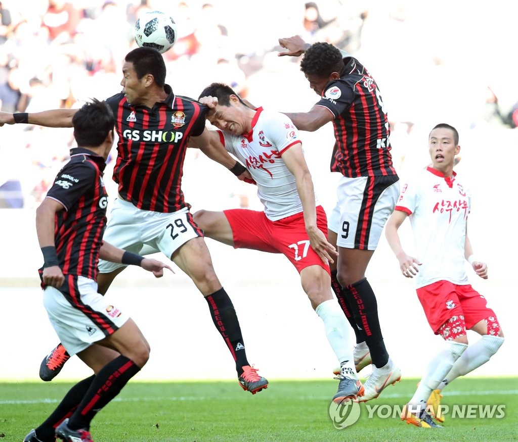 In this file photo taken on Sept. 30, 2018, players from FC Seoul (in red and black) and Sangju Sangmu try to win the ball during a K League 1 match at Seoul World Cup Stadium in Seoul. (Yonhap)
