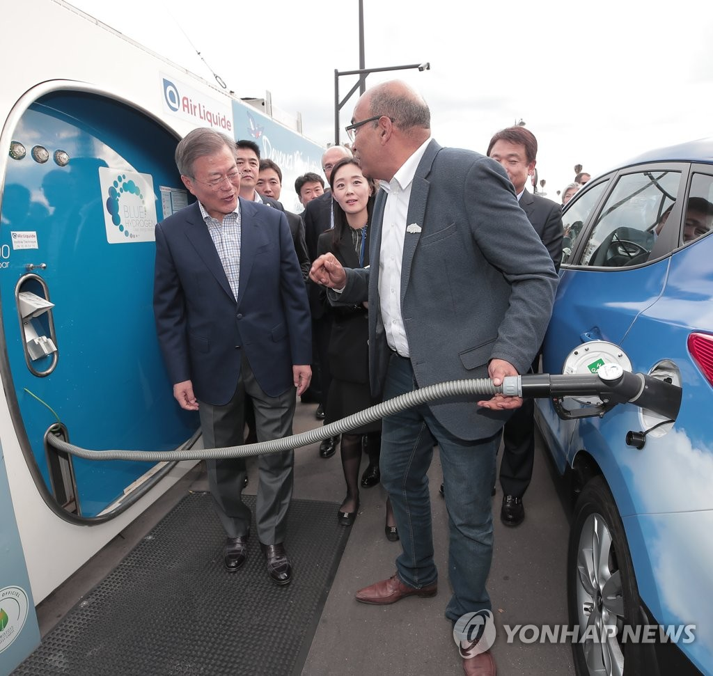 President Moon Jae-in (L) speaks with a taxi driver during a visit to a hydrogen refueling station on a square in central Paris during his state visit to France on Oct. 14, 2018. (Yonhap)