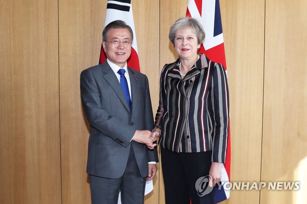 South Korean President Moon Jae-in (L) and British Prime Minister Theresa May shake hands before the start of their bilateral summit held on the sidelines of the Asia-Europe Meeting in Brussels on Oct. 19, 2018. (Yonhap)