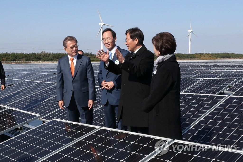 President Moon Jae-in (L) visits a floating solar farm in Gunsan on Oct. 30, 2018, after announcing his renewable energy vision. Song Ha-jin (2nd from L), governor of North Jeolla Province; Sung Yun-mo (2nd from R), minister of trade, industry and energy; and Kim Hyun-mi (R), minister of land, infrastructure and transport, accompanied him on his visit. (Yonhap)